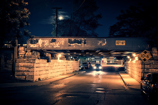Dark Chicago city street landscape with train bridge, alley, moon, dramatic sky, sidewalk and oncoming car with headlights on at night.
