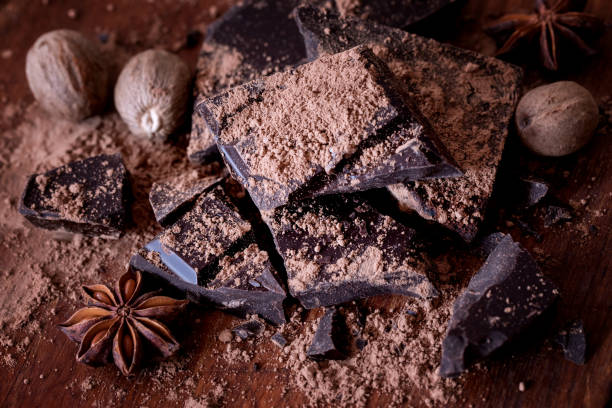 Dark chocolate bar crushed and sprinkled with cocoa powder with spices stock photo