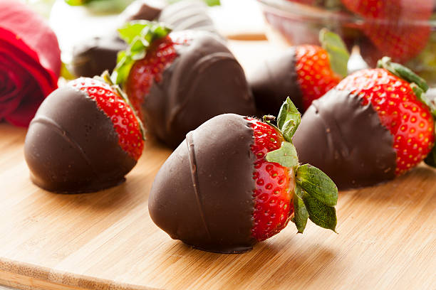 dark chocolate covered strawberries lying on a cutting board - aardbei stockfoto's en -beelden