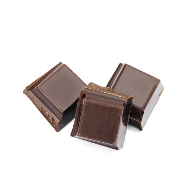 dunkle schokolade würfel isoliert auf weißem hintergrund. - low carb süßigkeiten stock-fotos und bilder
