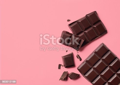 Dark chocolate on pink background. Top view