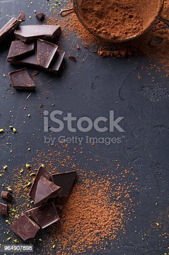 istock Dark chocolate pieces and cocoa powder over black background 964907898