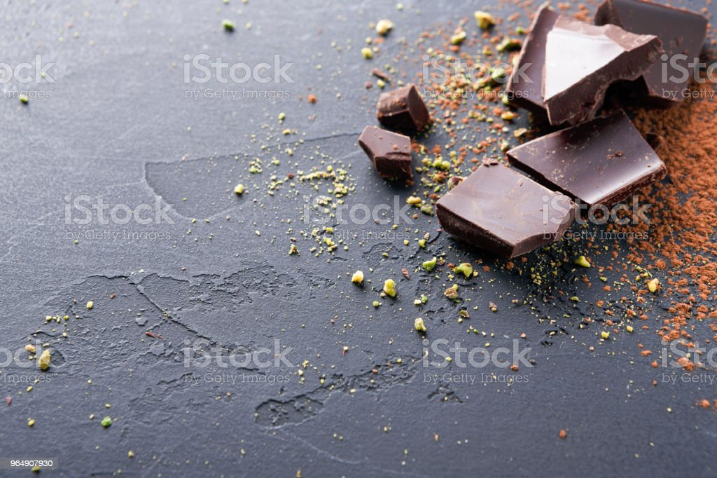 Dark chocolate pieces and cocoa powder over black background royalty-free stock photo