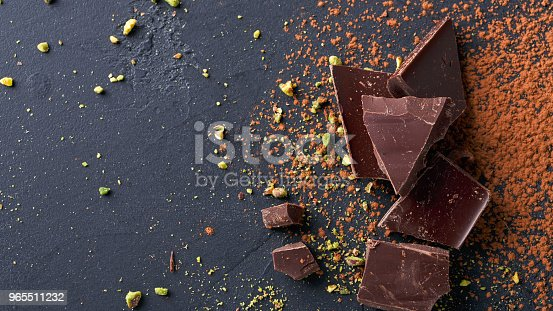 istock Dark chocolate pieces and cocoa powder over black background 965511232