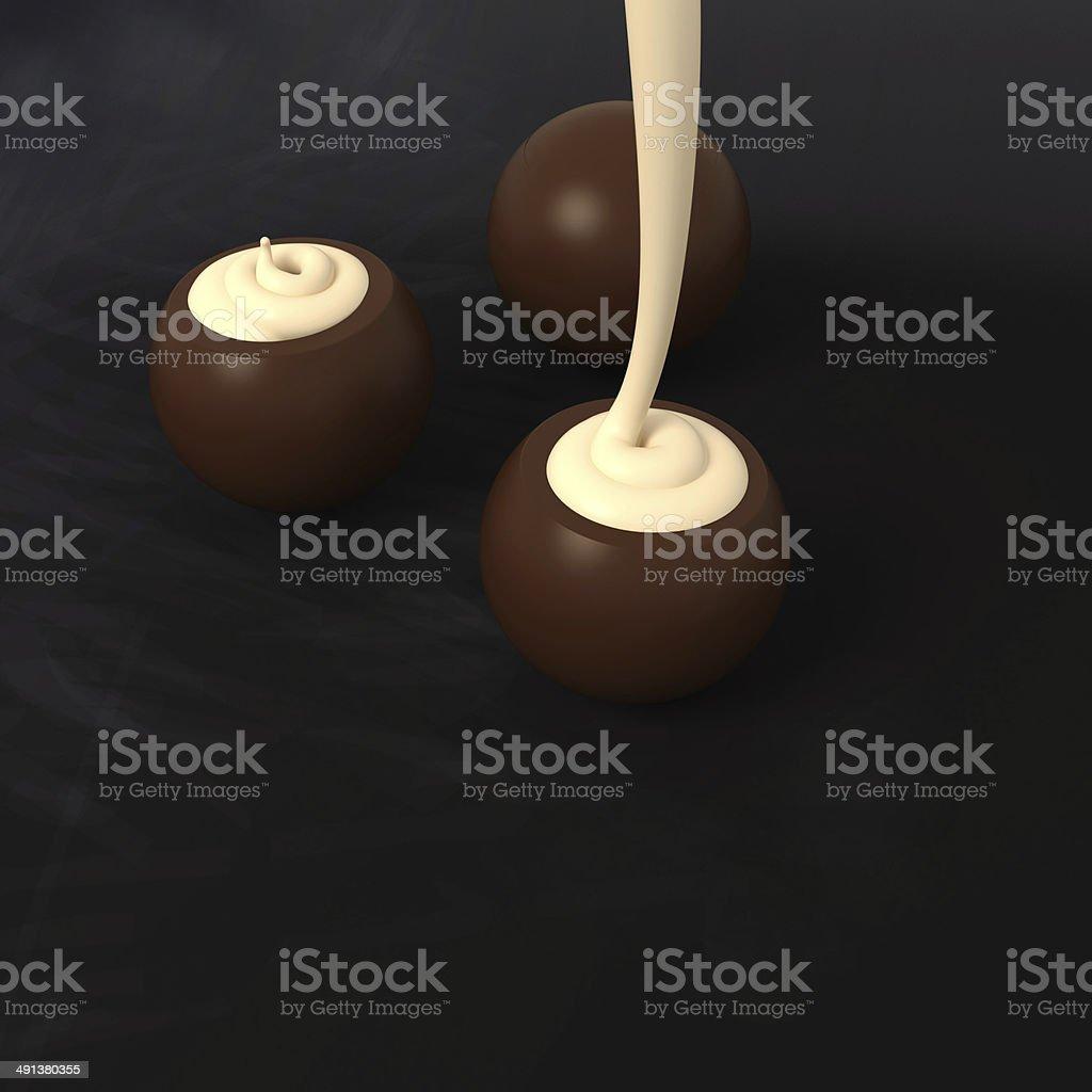 Dark chocolate pralines with vanilla cream filling on blackboard stock photo