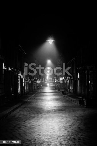 Dark city alley at night lit up with lamps
