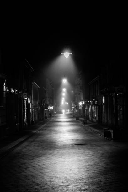 Dark city alley lit up by street lamps Dark city alley at night lit up with lamps alley stock pictures, royalty-free photos & images