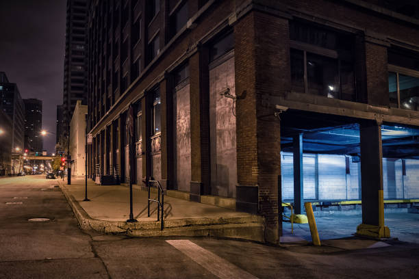 Dark city downtown street corner with an industrial warehouse loading dock at night. Dark city downtown street corner with an industrial warehouse loading dock at night. alley stock pictures, royalty-free photos & images