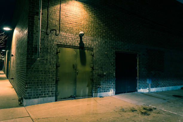 Dark city street corner and alley with an industrial building entrance at night stock photo