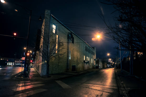 Dark city street corner and alley with an industrial building at night stock photo