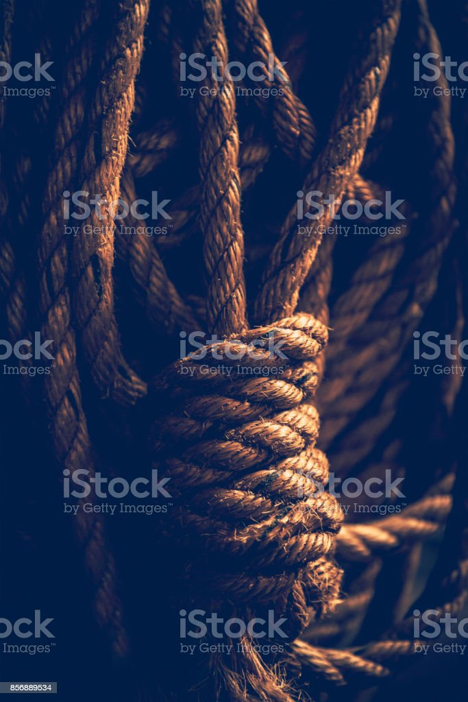 Dark closeup photo of a rope knot stock photo