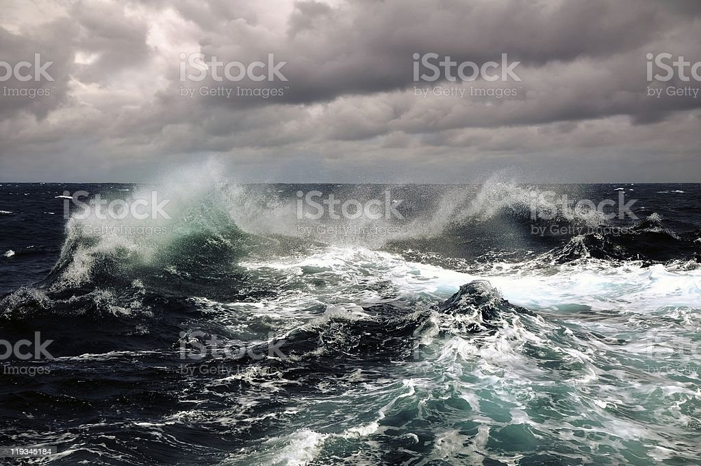 Dark clouds and crashing ocean waves stock photo
