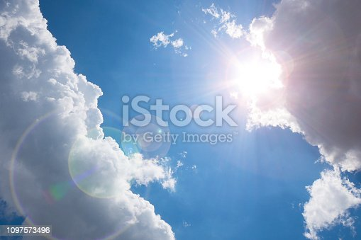 Dark clouds on blue sky with sunlight and flare.