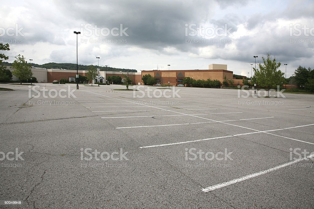 Dark clouds over an abandoned shopping mall stock photo