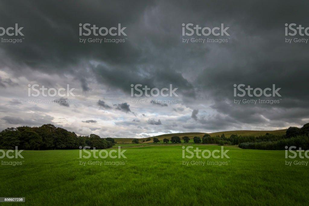 Donkere wolken boven de groene platteland Engeland foto