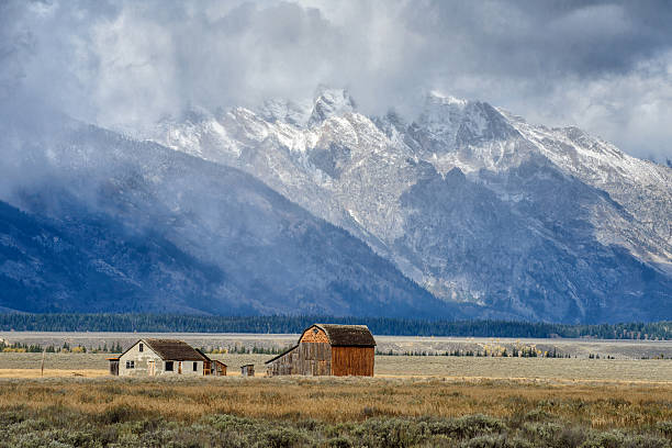 dark clouds  over mormon row in grand teton - great plains stock photos and pictures
