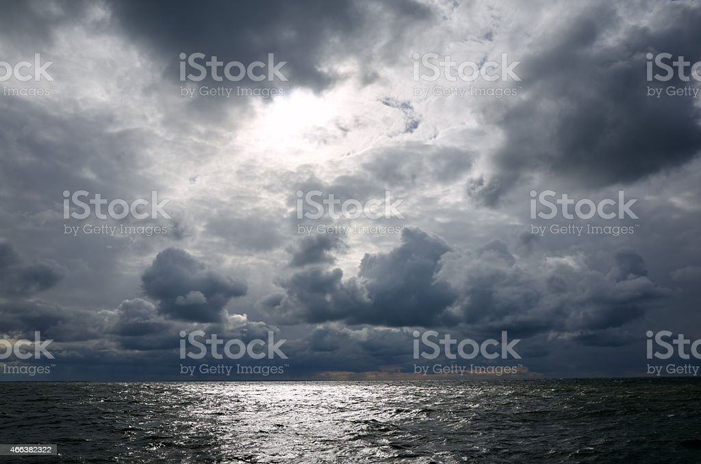Dark clouds passing over the ocean and hiding the sun stock photo