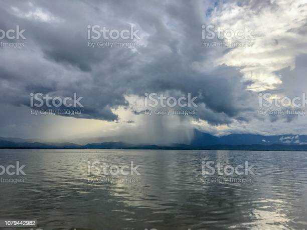 Photo of Dark clouds with rainy in storm day on the lake and mountain background. Raindrop only some area. Soft focus of clouds.