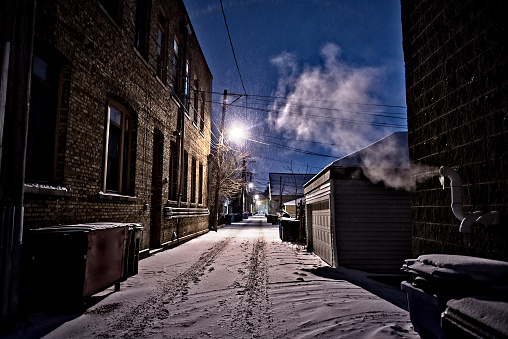 Dark, cold Chicago winter alley with snow, ice and a steaming vent at night.