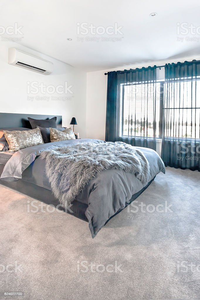 Dark color bedding items in a luxury bedroom stock photo