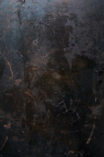 Dark colored metal surface with stains