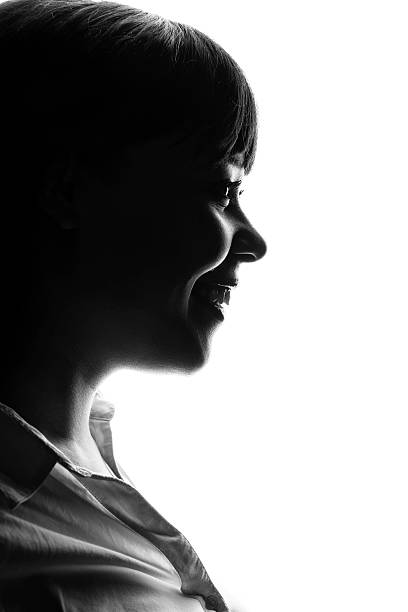 dark colored profile of smiling woman - high contrast stock pictures, royalty-free photos & images