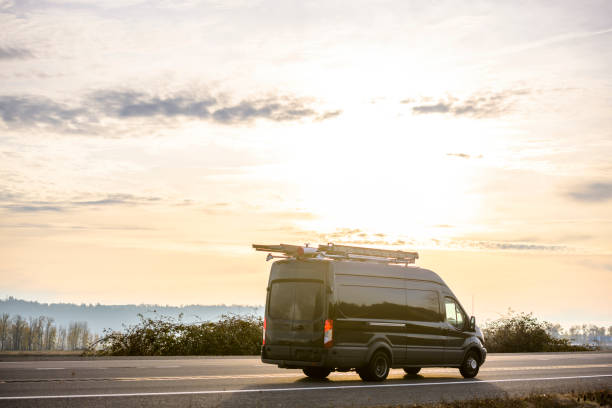 Dark compact cargo mimi van with ladders on the roof running on the road at sunset time stock photo