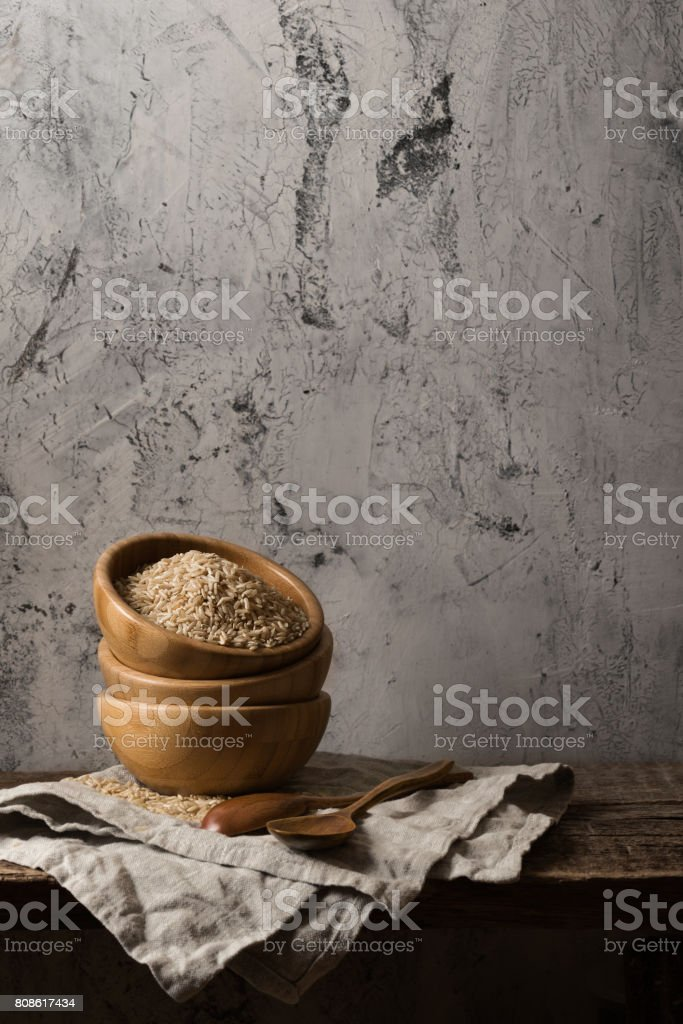 Dark composition with brown rice stock photo