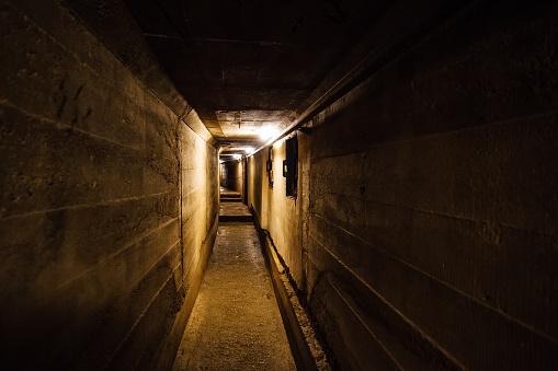 Dark corridor of old underground Soviet military bunker under artillery fortification.