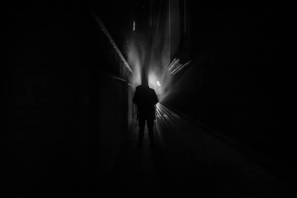 Dark corridor with cabinet doors and lights with silhouette of spooky horror person standing with different poses. – zdjęcie