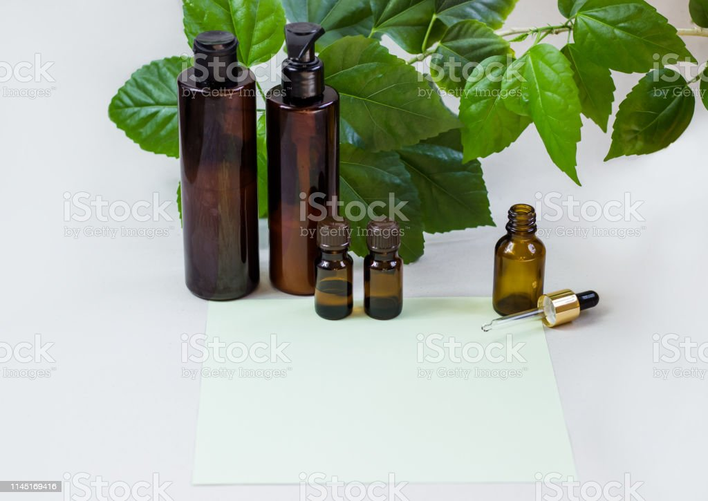 Dark cosmetic bottles and green natural leaves on a light background....