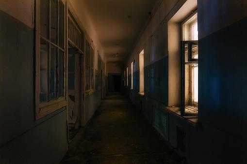 Dark creepy corridor of abandoned hospital at night. Horror concept