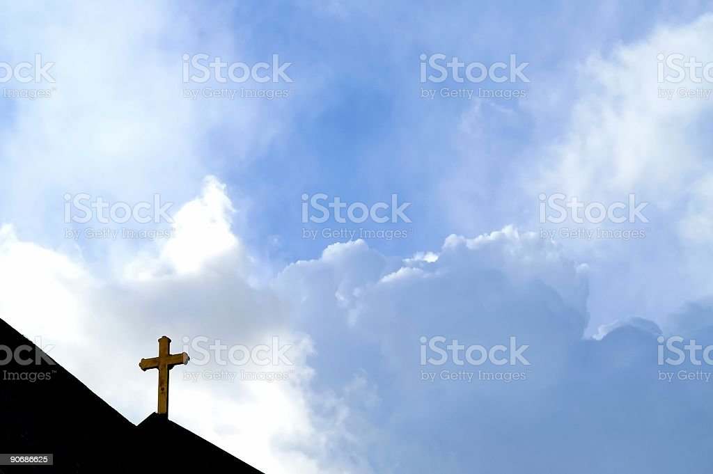 A dark cross against a blue sky  stock photo