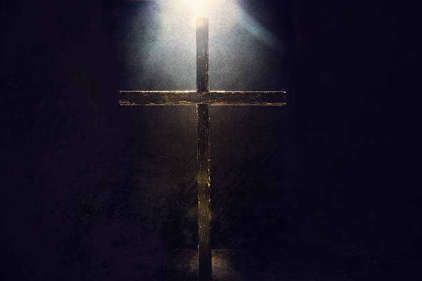 Dark Cross with Light Overhead A crucifix in a dark grunge setting is illuminated from above and behind by a bright and shining heavenly light.  Imagery intended to represent the crucifixion and resurrection of Jesus Christ celebrated on Easter sunday.  Horizontal image with copy space. religious cross stock pictures, royalty-free photos & images