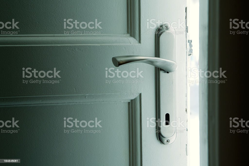 Dark door with blue-green glow behind stock photo