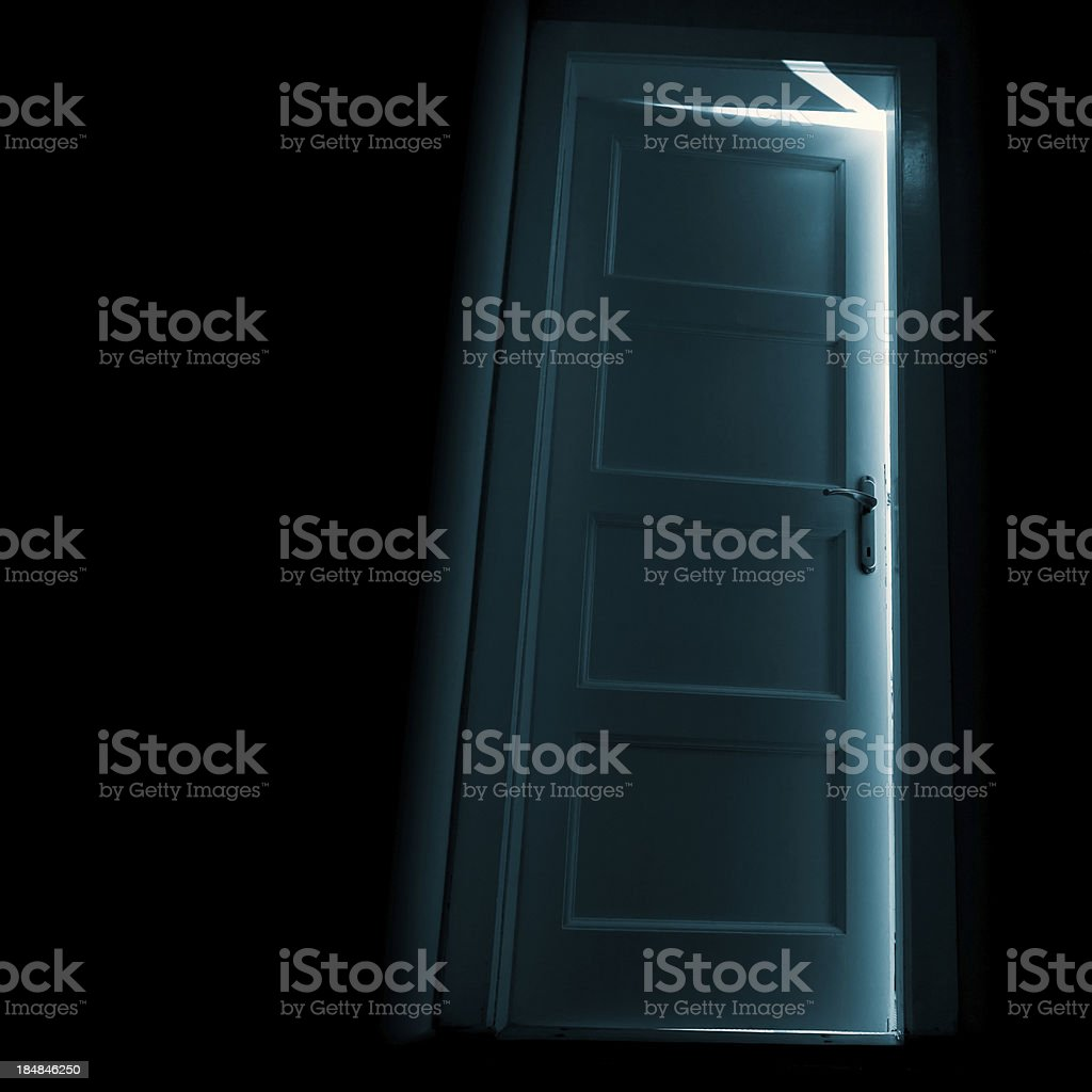 Dark door with glow behind stock photo