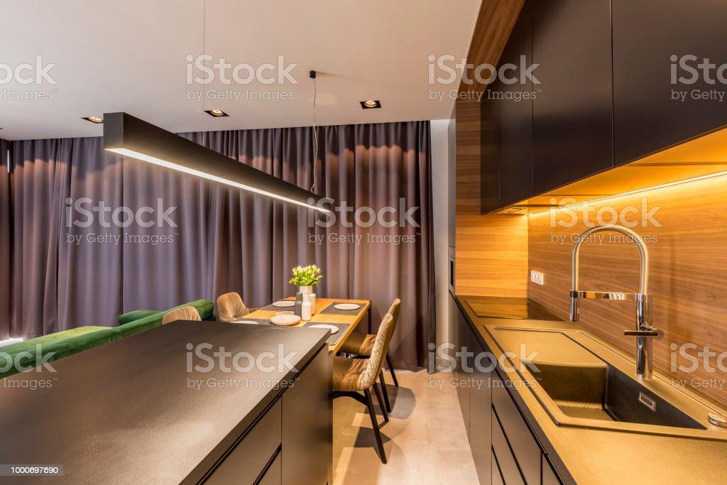 Dunkle Vorhange Hangen In Modernen Kuche Interieur Mit Schwarzen Regalen Und Arbeitsplatte Tisch Und Stuhle Stockfoto Und Mehr Bilder Von Arbeitsplatte Istock