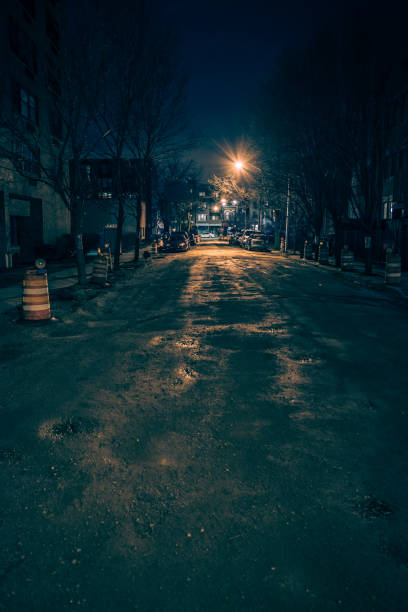 Dark empty and scary urban city street road with alleys under construction at night stock photo