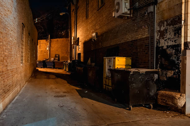 Dark empty scary urban city street alley with dumpsters and vintage buildings at night Dark empty scary urban city street alley with dumpsters and vintage buildings at night alley stock pictures, royalty-free photos & images