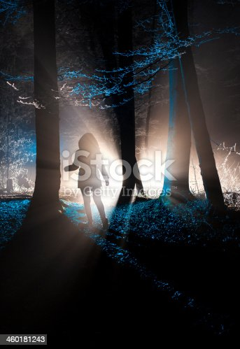 Dark silhouette walking in mysteriously illuminated forest on a foggy winter night
