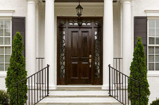 A grand entrance way leading up to an ornate dark wood door with green trees.