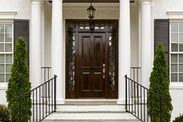 Dark front door with white columns A grand entrance way leading up to an ornate dark wood door with green trees. front door stock pictures, royalty-free photos & images