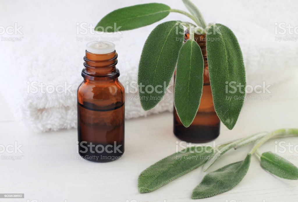 Dark glass aromatic essential oil bottle with fresh green natural sage plant leaves, white towel. stock photo