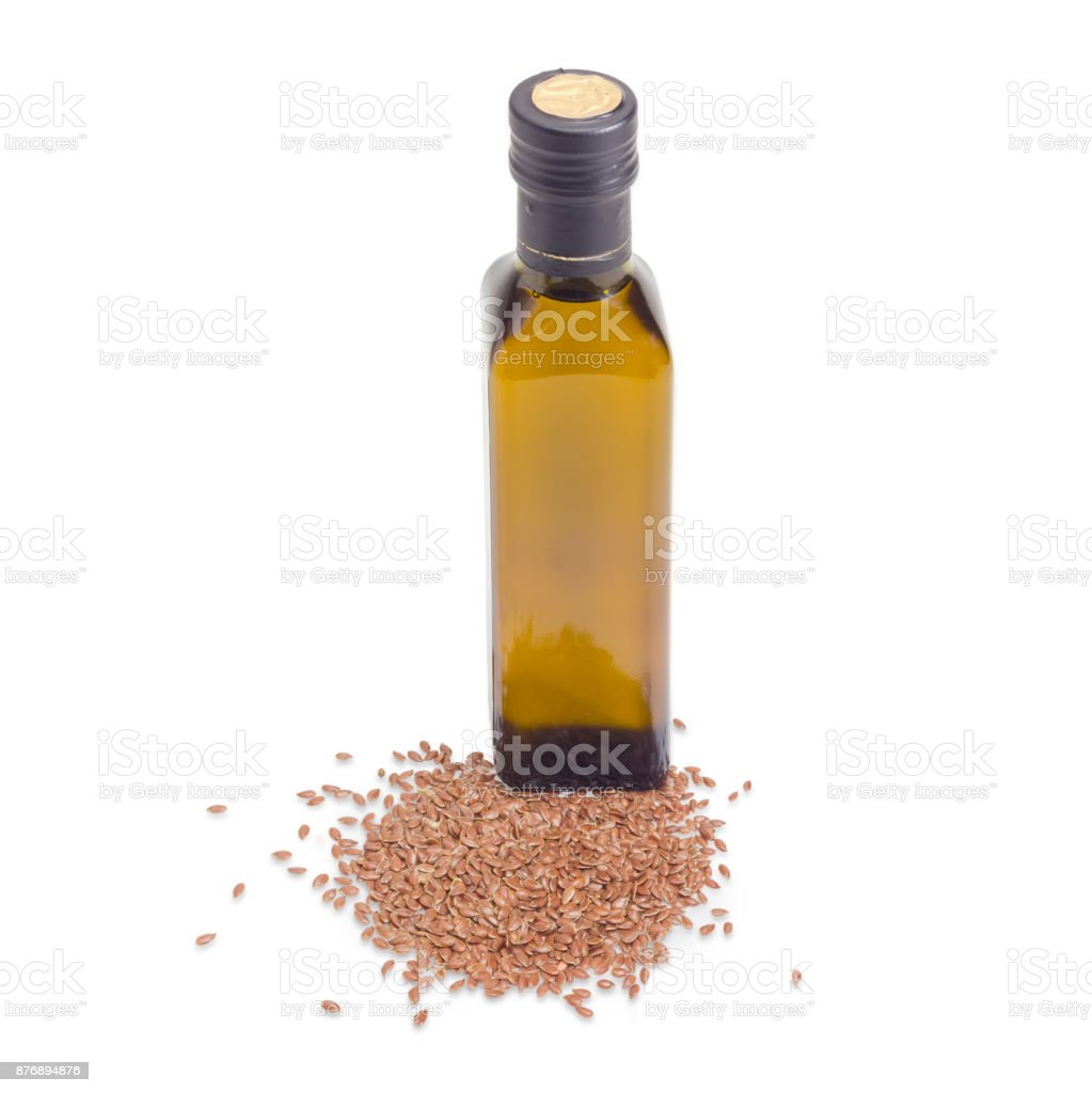 Dark gllass bottle of linseed oil and pile of linseed stock photo