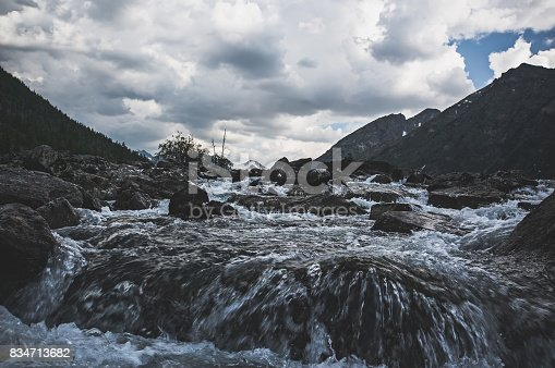 Dark gloom mountain valley along the mountain river on the background of snow peaks and ice glacier, Altai mountains, Siberia, Russia