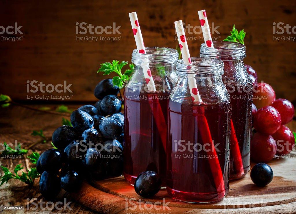 Dark grape juice in glass bottles with straws stock photo