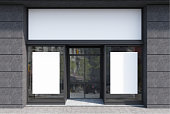 Dark gray and white cafe facade, two posters
