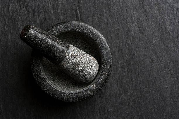 Dark gray granite mortar and pestle set on textured counter stock photo