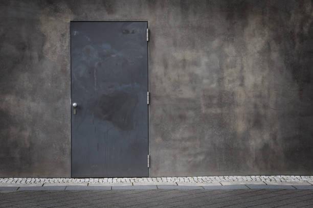 Dark gray steel door and rough concrete wall stock photo