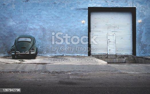 istock Dark green vintage Volkswagen beetle parking at abandoned blue building with garage gate, Merida, Yucatan, Mexico 1267942796